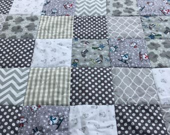 Patchwork crib quilt in greys with sheep, elephant and fox detail. White minky backing.
