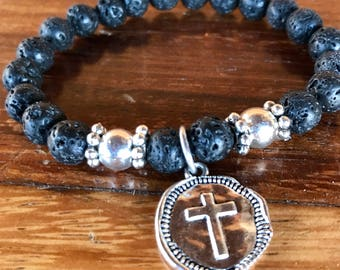 Handmade stretch yoga bracelet in black lava stone with center hammered cross charm. Perfect for essential oil diffusing.