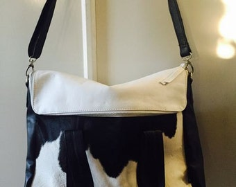 Cow hide shoulder bag featuring lambskin leather. A unique and versatile tote which holds everything. Lined and handmade quality.