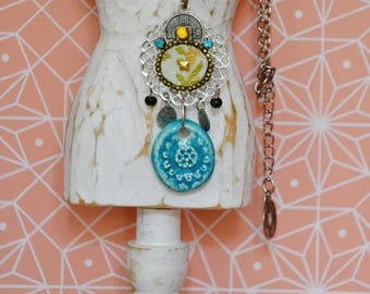 Medallion in metal and silk with a turquoise raku bead
