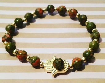 "6mm semi precious stone beads with a gold plated Hamsa Hand. Model's wrist is 6.5""."