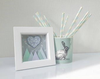 Framed paper art decoration, heart and mountain design.