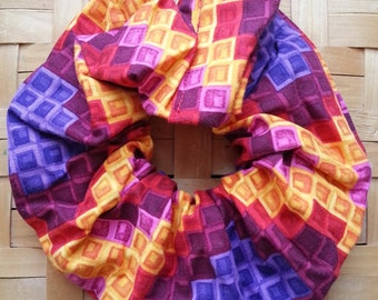 Hair Scrunchie with multi-colored blocks in oranges, reds, and purples