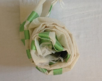 Handwoven cotton scarf with green stripes on either end.