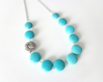 turquoise gem necklace with a silver swirl shell