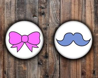 Género revelan pins.  Bigote azul y lazo rosa.