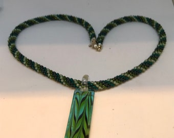 Teal and green beaded Kumihimo necklace with glass pendant.