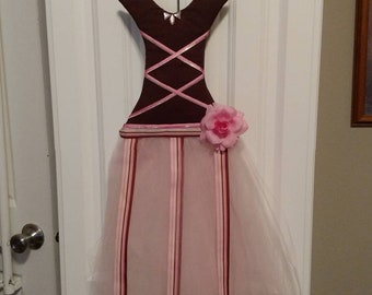 Pink and brown bow, barrette, and clip holder shaped like a long dress or ballerina outfit. 3 ribbons for holding and ribbons on body.