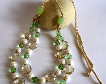 Double necklace made with green glass crystals and white glass beads. Closure with adjustable cotton cord.
