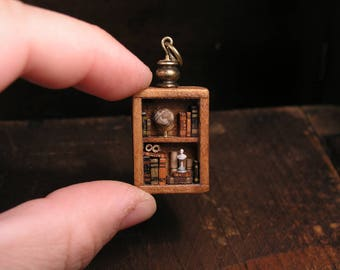 Miniature library pendant, full of tiny books, parchments, a globe and a bust