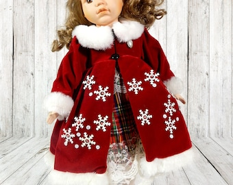 Porcelain doll in red velvet dress embellished with snowflakes and sequins