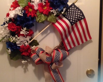 """26"""" Grapevine Red White and Blue floral wreath with USA flag in center and bow at bottom"""