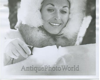 Pretty woman with GE light bulb in snow vintage photo