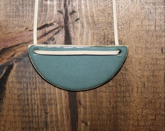 Teal ceramic pendant on a faux suede cord