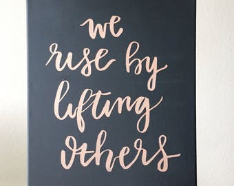 We rise by lifting others / positive inspirational uplifting quote/ rose gold/ canvas/calligraphy/hand lettered