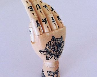 Hand mannequin with original hand drawn tattoo style illustrations