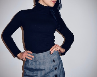 Pocket-shaped skirt with button closure.