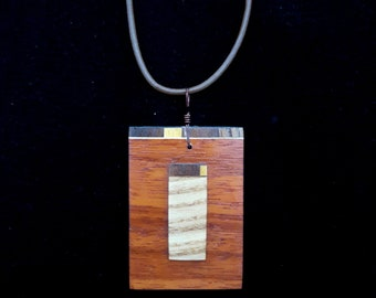 Wooden necklace that can be worn as a pendant on a strip of leather, or at the neck on a hoop.