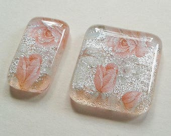 Pair of silver dichroic glass cabochons with pink rose patterns.