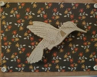 White Hummingbird embossed on Kraft colored paper