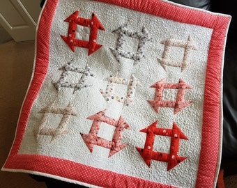 Hand made square baby churn dash patchwork quilt with free motion quilting in pink and white.
