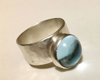 Simple hammered silver ring with blue topaz Carbochon