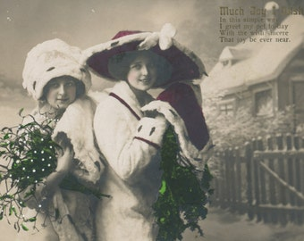 Hand colored  photo postcard of pretty girls in a winter scene. RPC, RPPC
