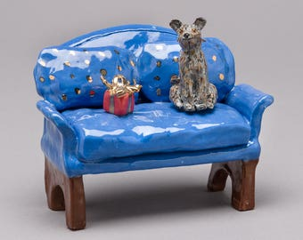 "Ceramic sculpture, clay hand built ""Scruffy dog"" on sofa with present."