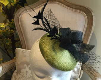 Beautiful green fascinator base with black loops, netting and feathers. Gorgeous on!
