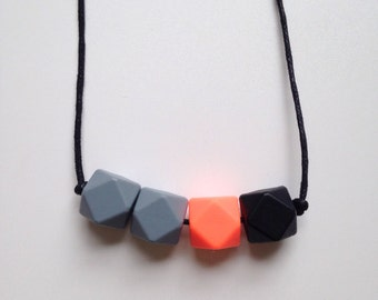 Teething necklace in grey, neon orange and black, made from BPA free chewable silicone hexagon beads by Little Gnashers
