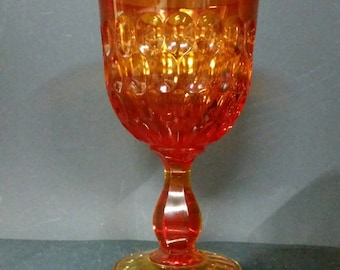 Vintage amberina color pedestal goblet vase. Thumbprint pattern