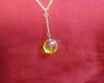 Yellow pendant on gold chain necklace