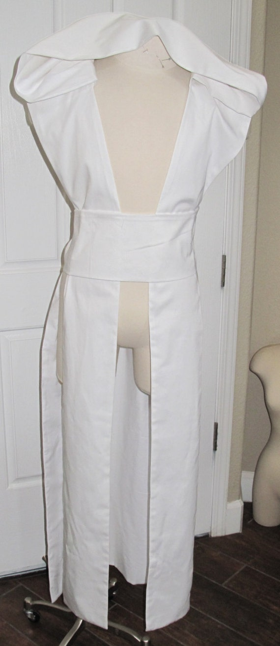 White sleeveless hooded tabard vest with a sash in several sizes