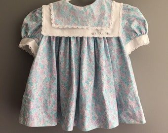Vintage floral bibbed dress with delicate trim and rosettes by Polly Flinders