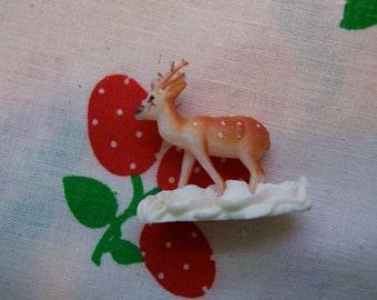 tiny plastic deer figurine with antlers