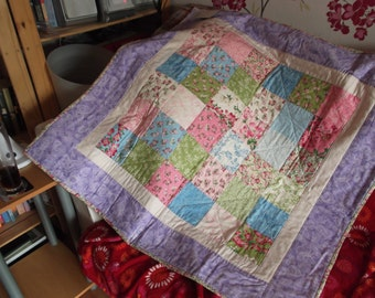 Pink lilac and blue lapquilt made from cotton with a polycotton lining.  Machine pieced and hand quilted