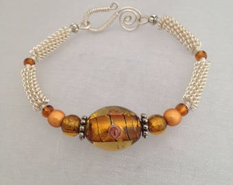 Silver wirework bracelet, with amber coloured lampwork focal bead.