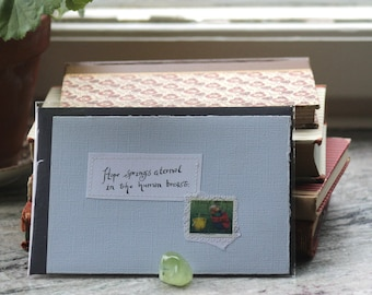Hope springs eternal in the human breast Pale blue card with handwritten quote and Swedish postal stamp