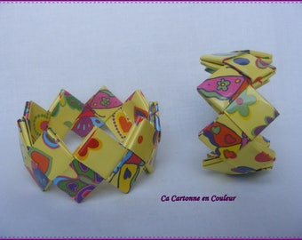 Bracelet closed multicolored recycled paper on a pale yellow background