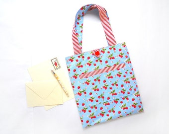 Reversible cotton tote bag/book bag with pockets with red strawberries on a light blue background; and red and white stripes on reverse side