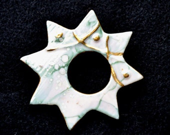 "Brooch, Starburst Iridescent,Green/White 3""   Ceramic. Raised Gold Trim."