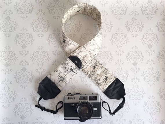 camera with travel themed camera strap on white fleur de lis wallpaper
