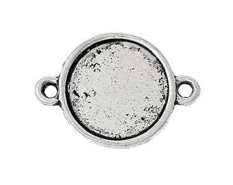 A connector finding in antique silver round cabochon.
