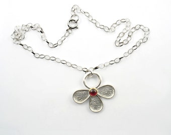 Half sterling silver flower pendant set with a cabochon stone in solid gold,holding on oval rolo sterling chain.Matching earrings and ring.