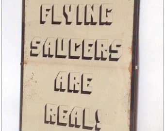 Aged reproduction print - Flying Saucers Are Real - in clip frame.