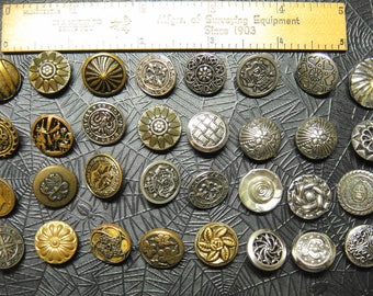 Thirty-two vintage silver and gold toned metal buttons