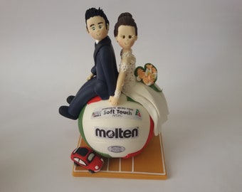 custom bride and  groom sitting on a volleyball wedding cake topper