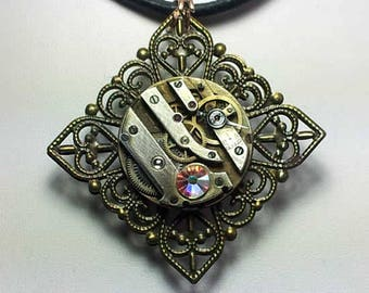 Steampunk  pendant, bronze colour filigree stamping, watch mecanism, Swarovski crystal cab , pink glass cab and  a  black leather  strap