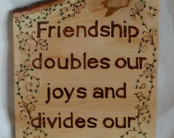 Friendship doubles our joys and divides our sorrows wood burned  and painted plaque with blue flowers, embellished with colored crystals.