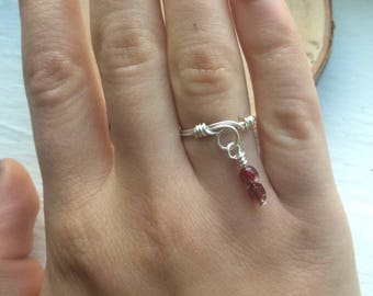 Silver rings with maroon dangling crystals